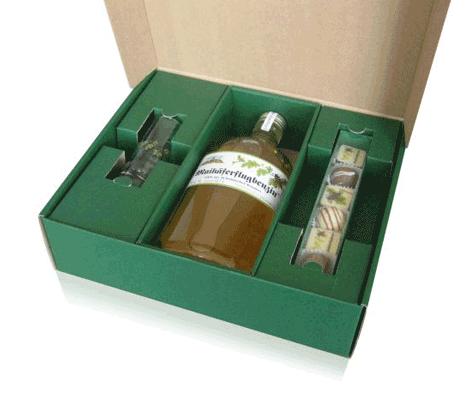 Geschenkverpackung für eine Flasche mit Glas und Pralinen